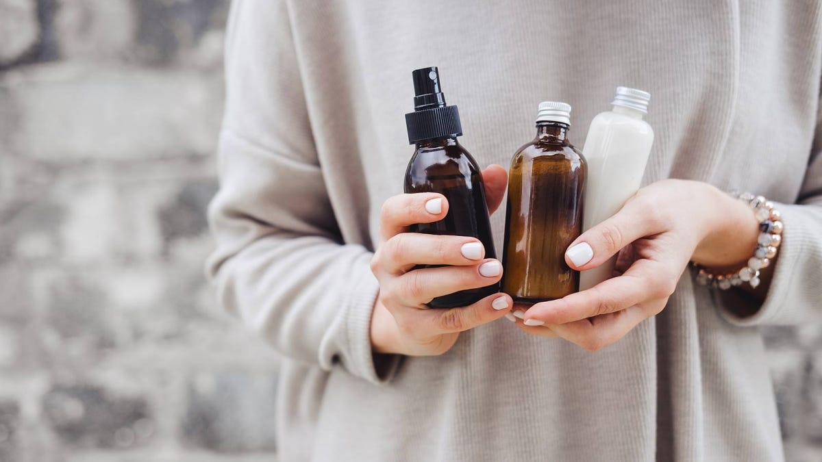 Woman holding bottles of her favorite spa skincare treatments.