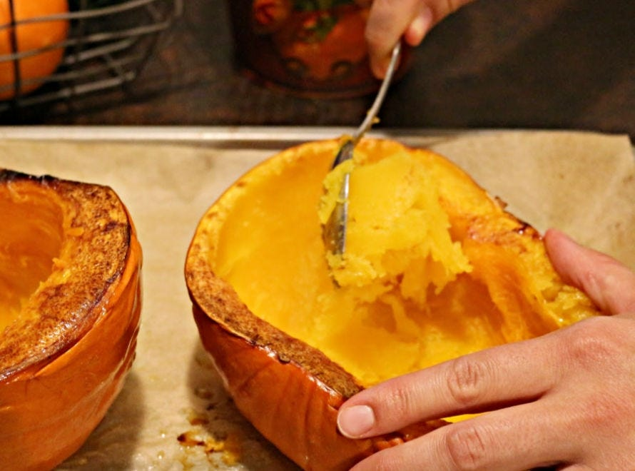 A hand using a spoon to scoop out a roasted pumpkin.