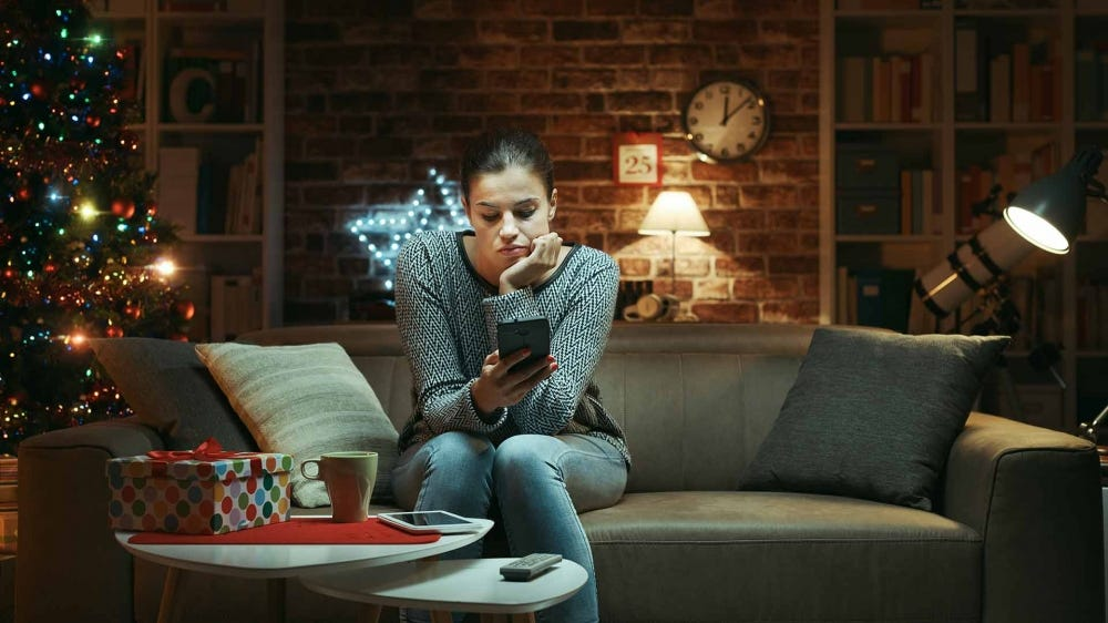 A woman looking at her smartphone, waiting to video chat with family over the holidays.