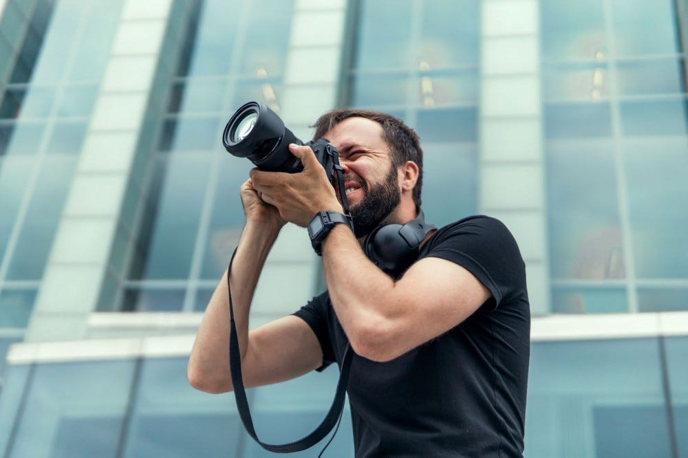 A male photographer lining up a shot in his camera.