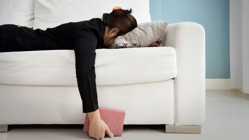 A woman lying facedown on a couch.