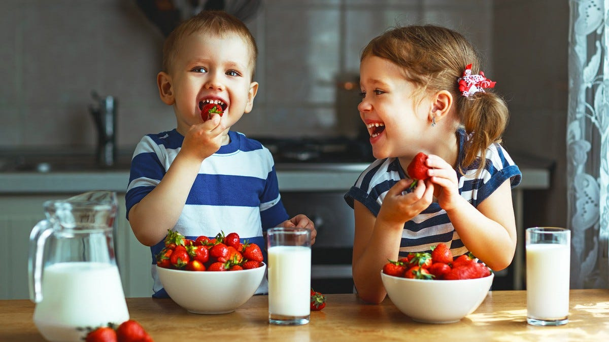 A little boy and girl eating strawberries out of two big bowls on a countertop next to two glasses of milk.