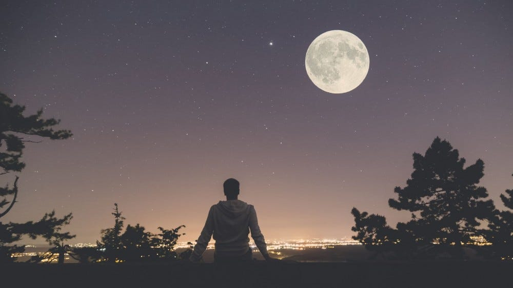 A young man sits on a wall at night looking at a full moon.