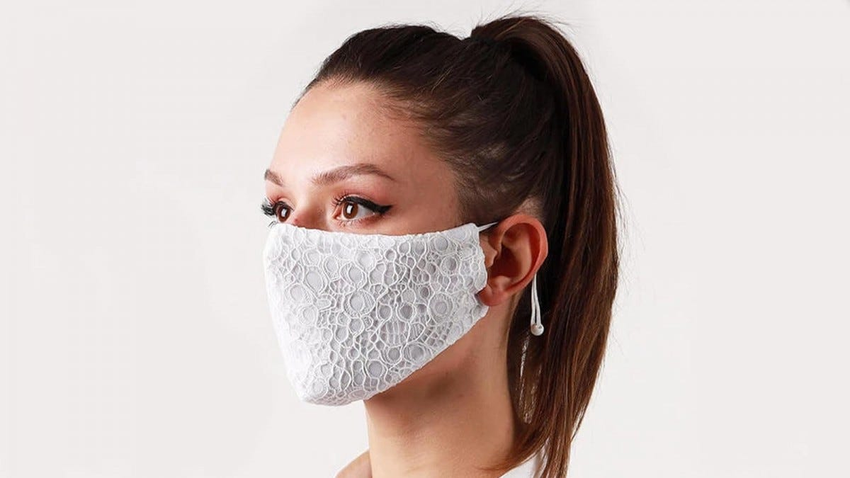 A woman wearing a pretty lace face mask from House of X.