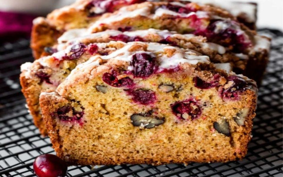 Freshly sliced, orange-glazed cranberry bread, sitting on a cooling rack.