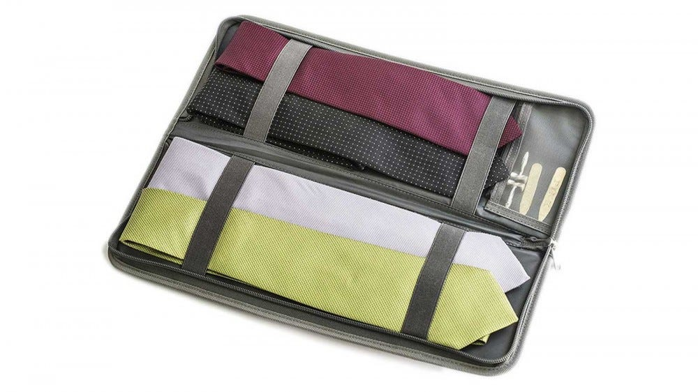 A travel tie case folded open, with several ties and clips tucked inside.
