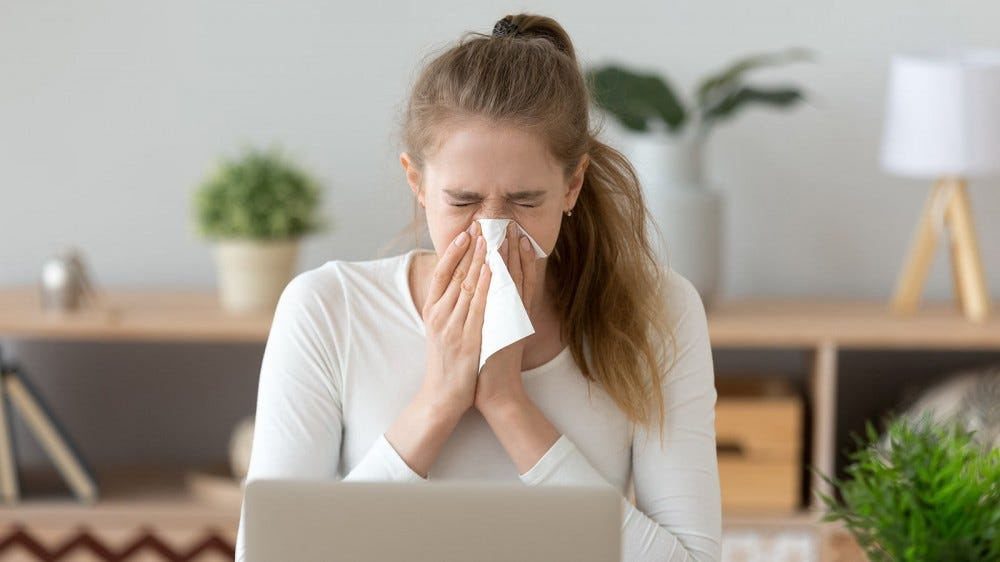 A woman suffering from seasonal allergies, blowing her nose.