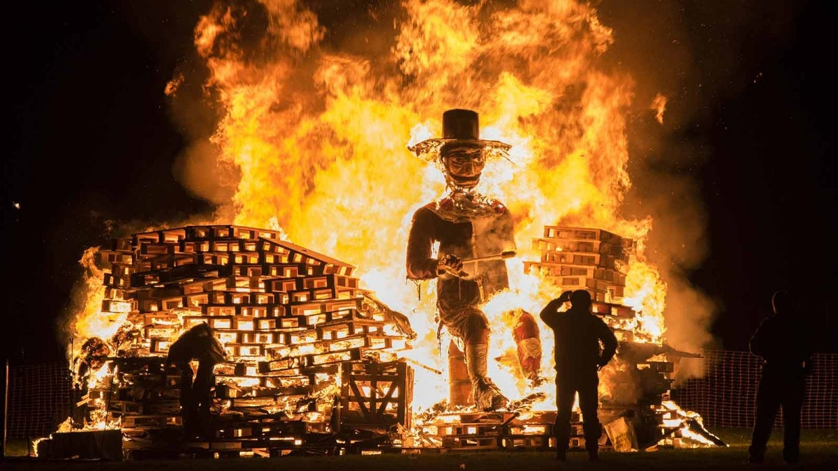 Man standing in front of a Guy Fawkes bonfire during the 5th of November at Lindifield bonfire night