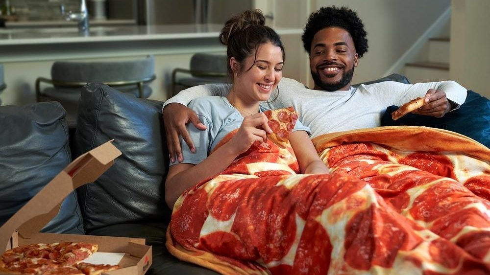 A couple sit on a couch eating pizza under a pizza patterned weighted blanket.
