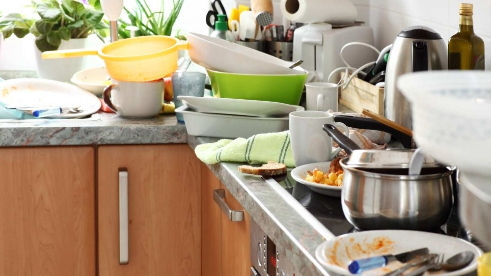A messy kitchen, piled high with dirty dishes.