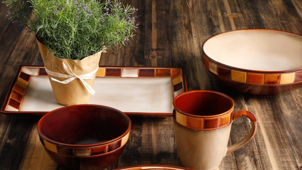 A matched set of earth-tone serving dishes on a wooden table.