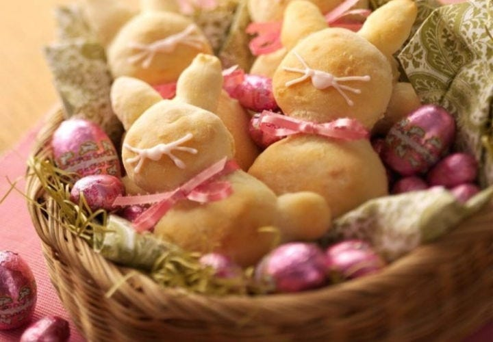 Small bunny rabbit shaped breads and chocolate Easter eggs all stuffed into an Easter basket.