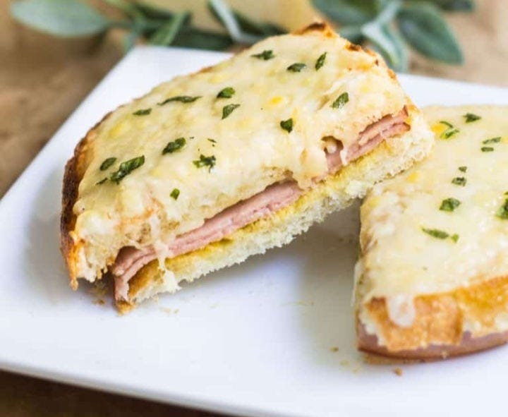 A hot and delicious croque monsieur sandwich topped with béchamel sauce.