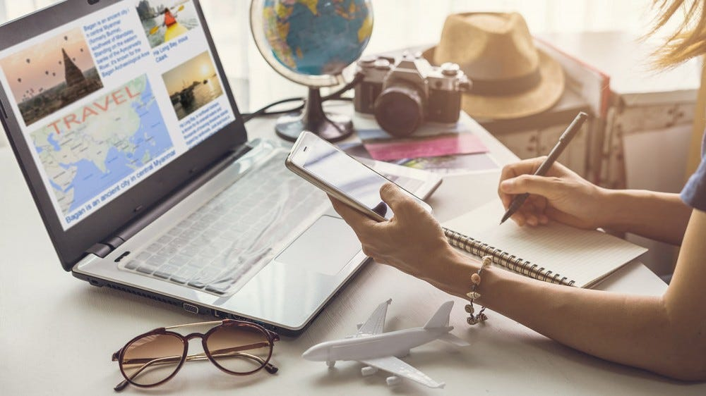 A woman using her laptop, phone, and a notebook to plan a trip.