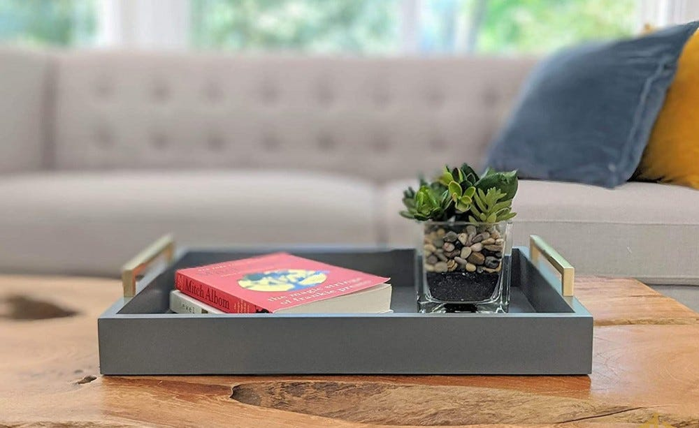 Gray tray sitting on a wood coffee table, with a book and a small plant in the tray