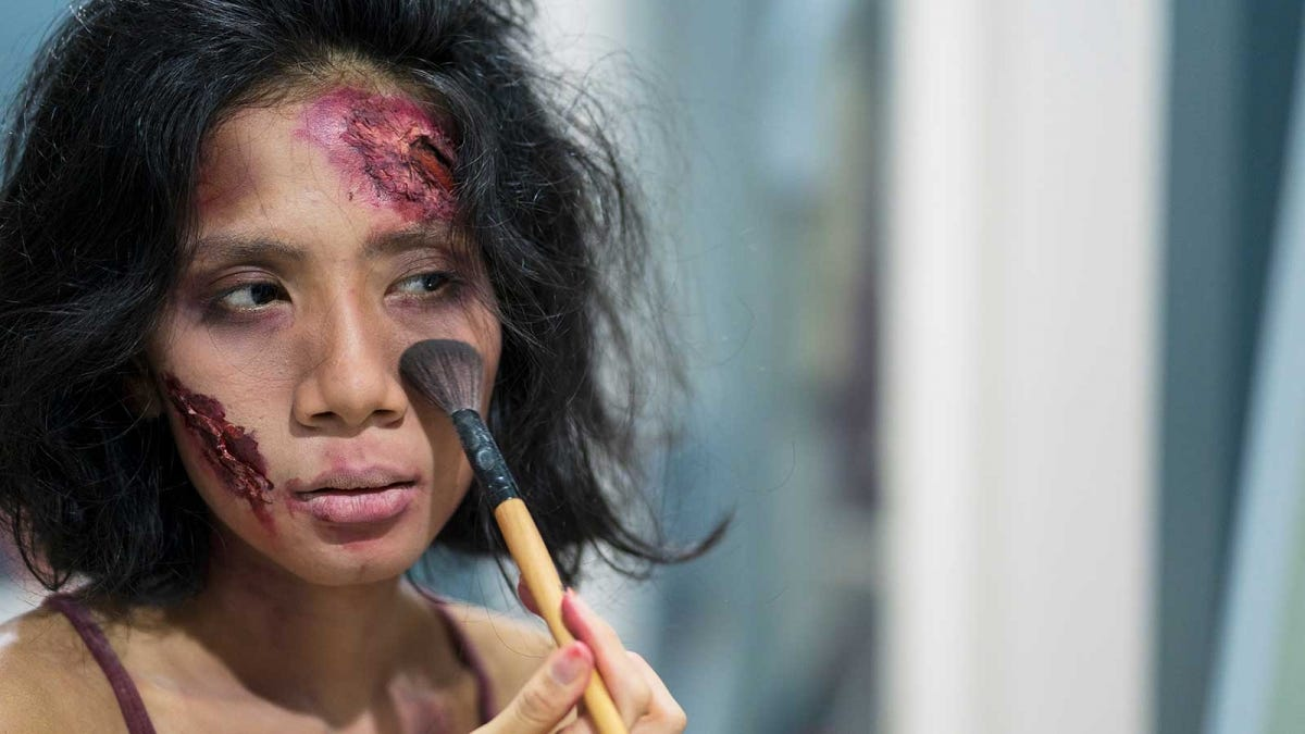 woman putting on special effects makeup to look like her face is injured