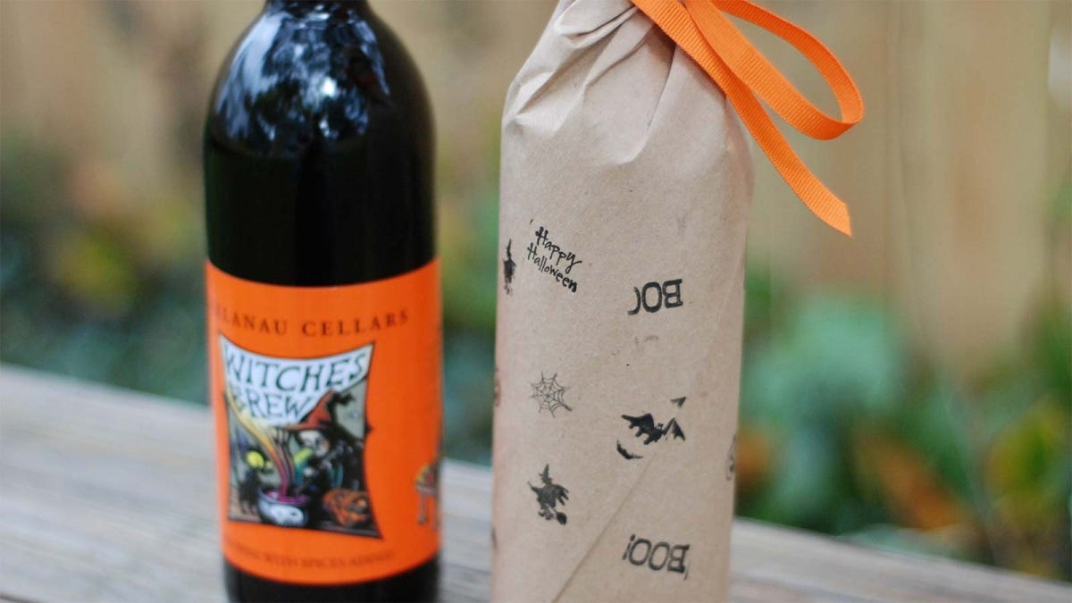 One bottle of Witches Brew spiced wine sitting next to another wrapped in Halloween craft paper.