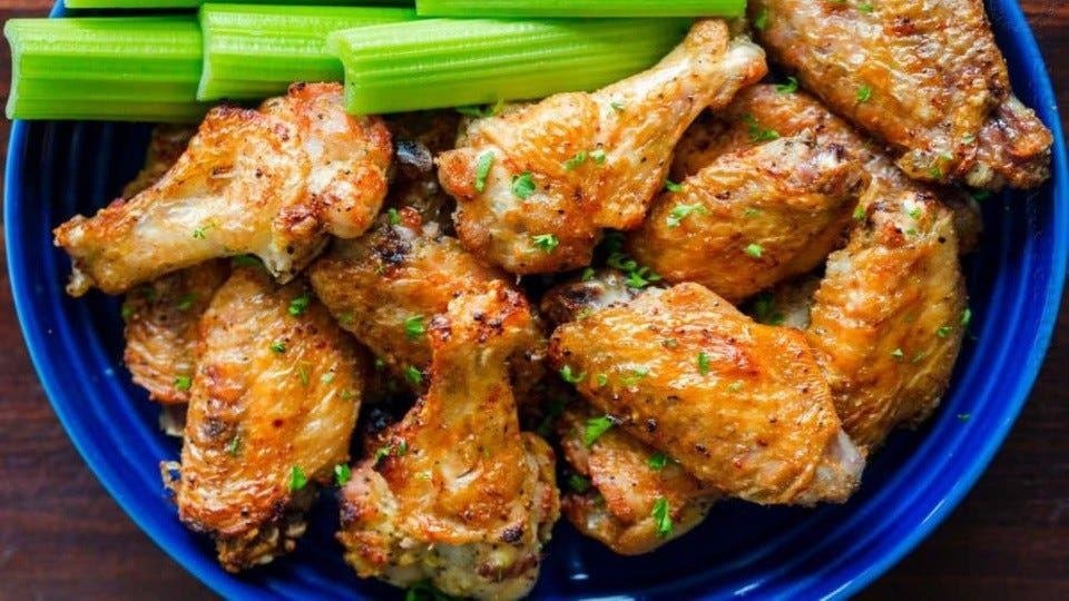 A bright blue bowl filled with crispy air-fried chicken wings, with a side of celery.