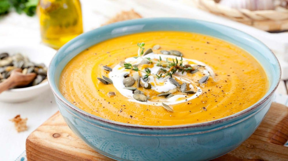 A bowl of pumpkin soup sprinkled with roasted pumpkin seeds.