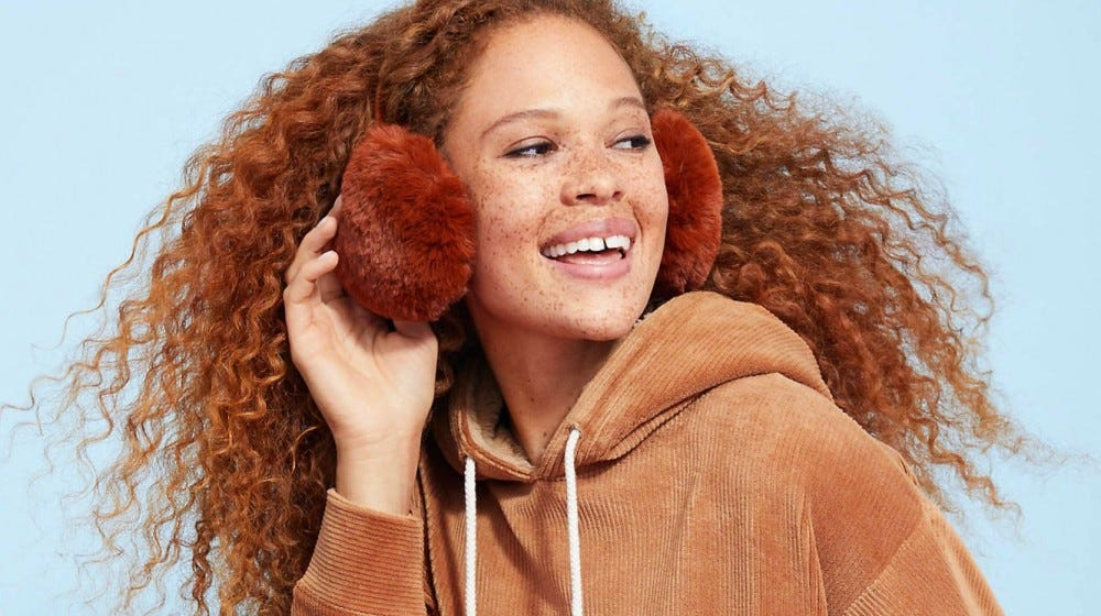 A smiling young woman wearing earmuffs and a tan corduroy sweatshirt.