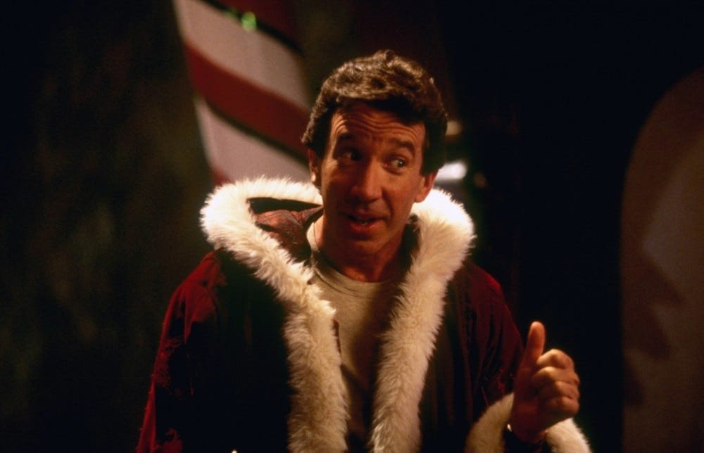 Tim Allen stands in front of a candy cane while wearing a Santa Claus jacket.