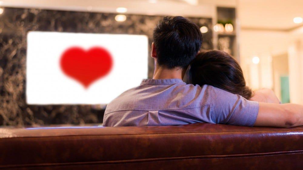 Egy pár a kanapén nézi a rom-com-ot.