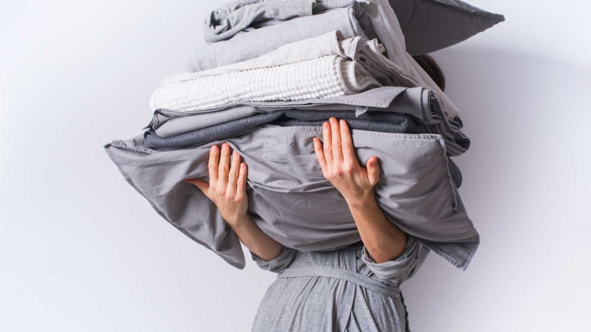 woman carrying all the linens for her bed