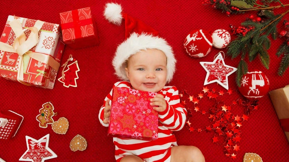 A baby wearing a Santa hat and holding a gift surrounded by Christmas decorations.