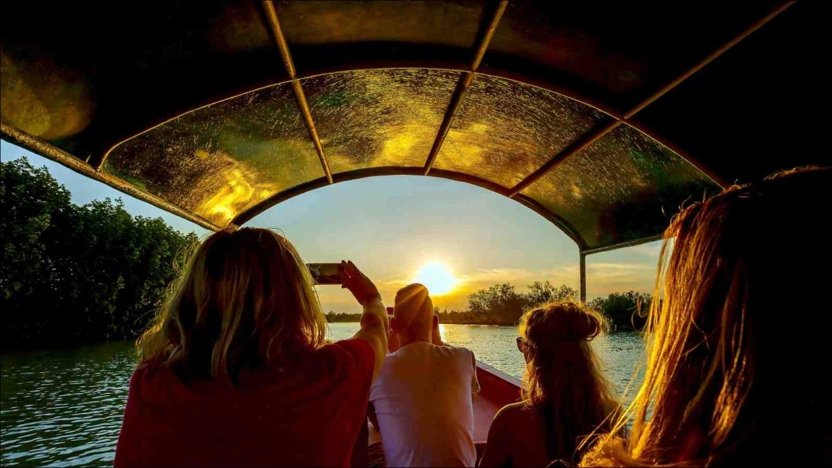 Tourists on long tailed boating tour in mangrove canal during sunset