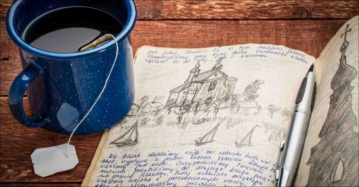 handwriting and drawing in pencil in a notebook against rustic picnic table with cup of tea