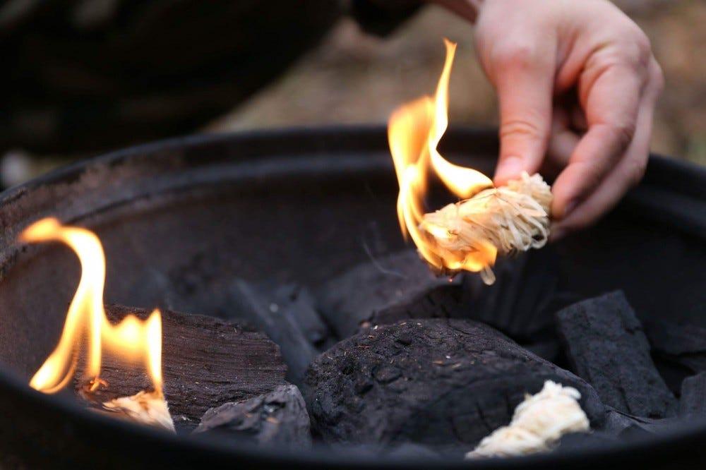 A camper starting a fire with a Yeti firestarter.