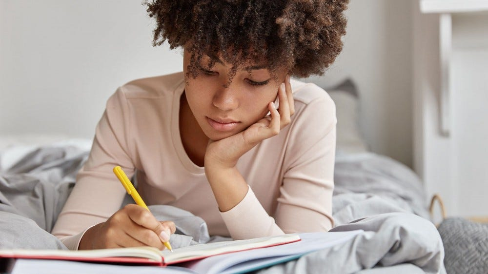 Woman writing down her dreams in a dream journal.
