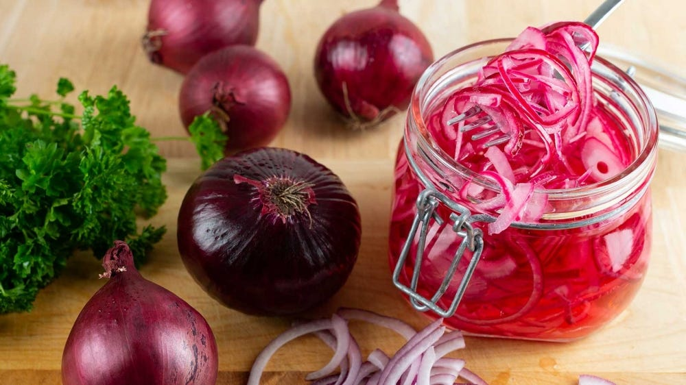 Fresh onions and sliced pickled onions in a bail-top jar, sitting on a counter.