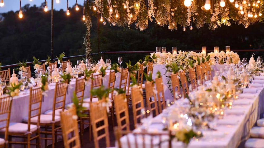 Large tables set up for a sizable outdoor wedding.