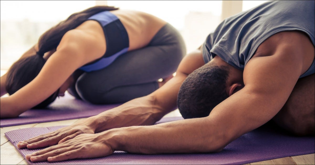 couple in sports clothes stretching on yoga mat