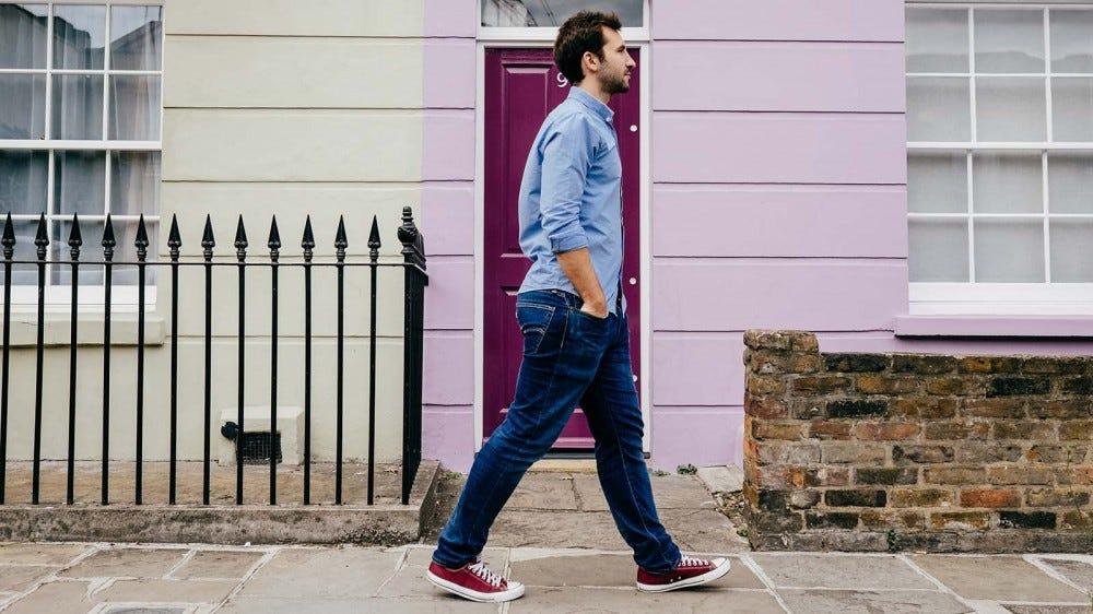 A man walking on a sidewalk in a residential area.