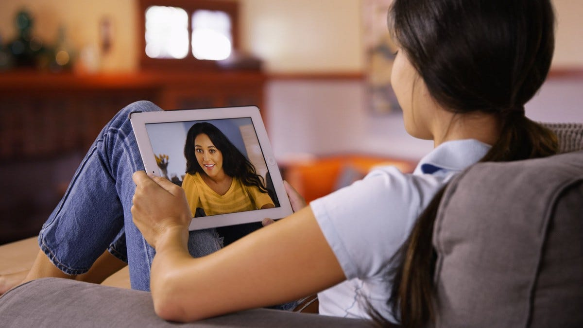 A young woman sitting on a couch talking to another woman on a video call on a tablet.