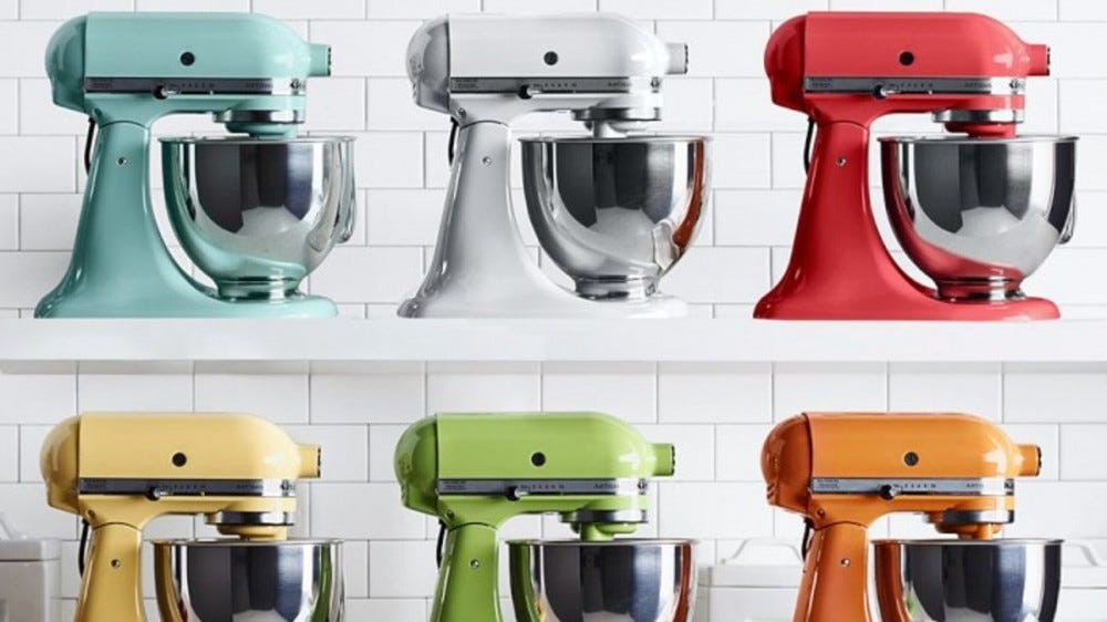 A row of multi-colored Kitchenaid mixers sit on a shelf.