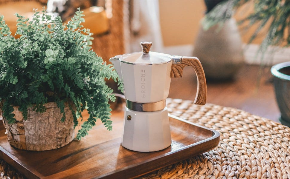 The Grosche Milano Moka Espresso maker sitting on a wooden tray next to a potted plant.