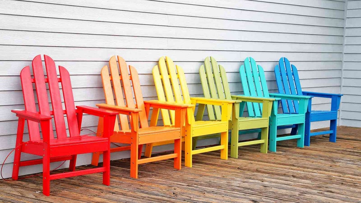 Colorful deck chairs, sitting on a wooden deck.