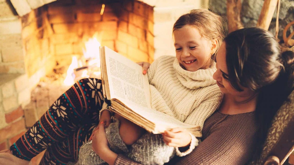 mom reading to her daughter by a cozy fire