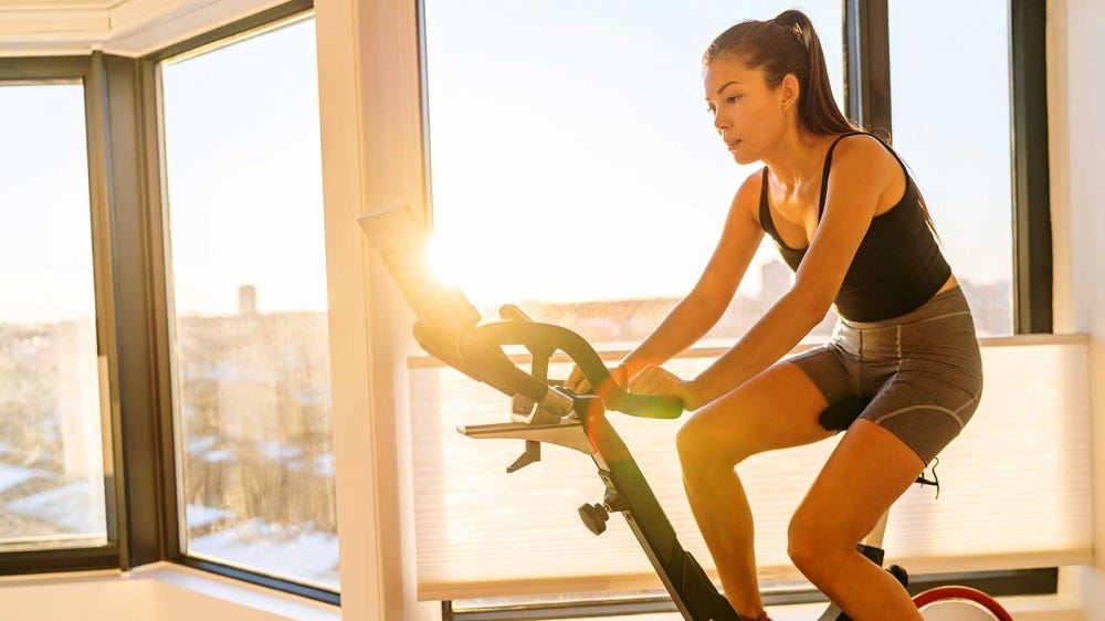 A woman pedaling on an exercise bike.