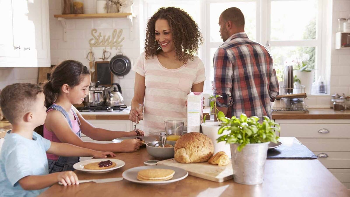 A mom standing next to the kitchen table where her kids are eating breakfast, while dad washes dishes behind them.