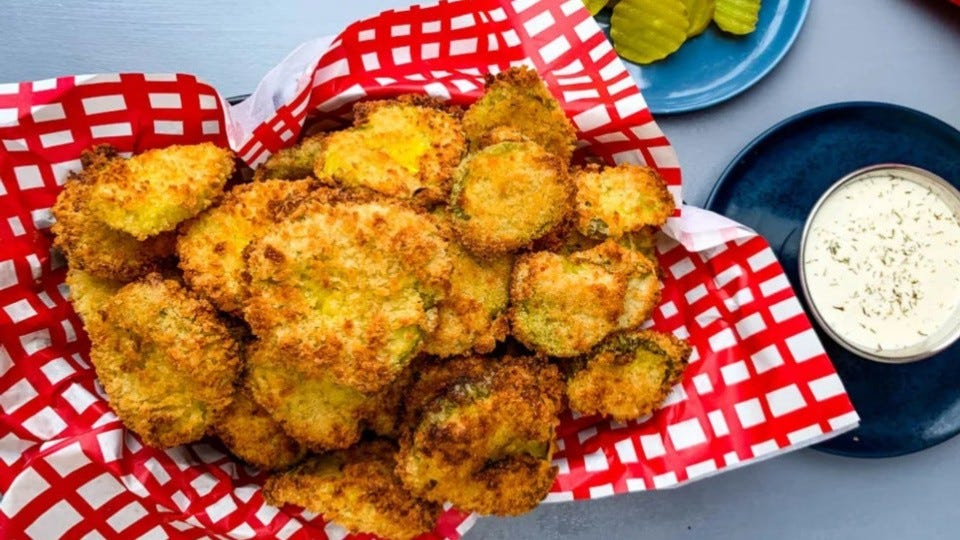 A basket lined with red and white parchment liner, filled with a heaping pile of fried pickles, served with a side of ranch.
