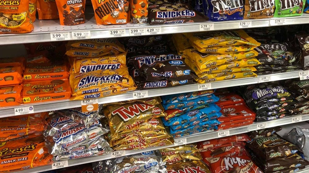 Bags of candy in the candy aisle at a grocery store.