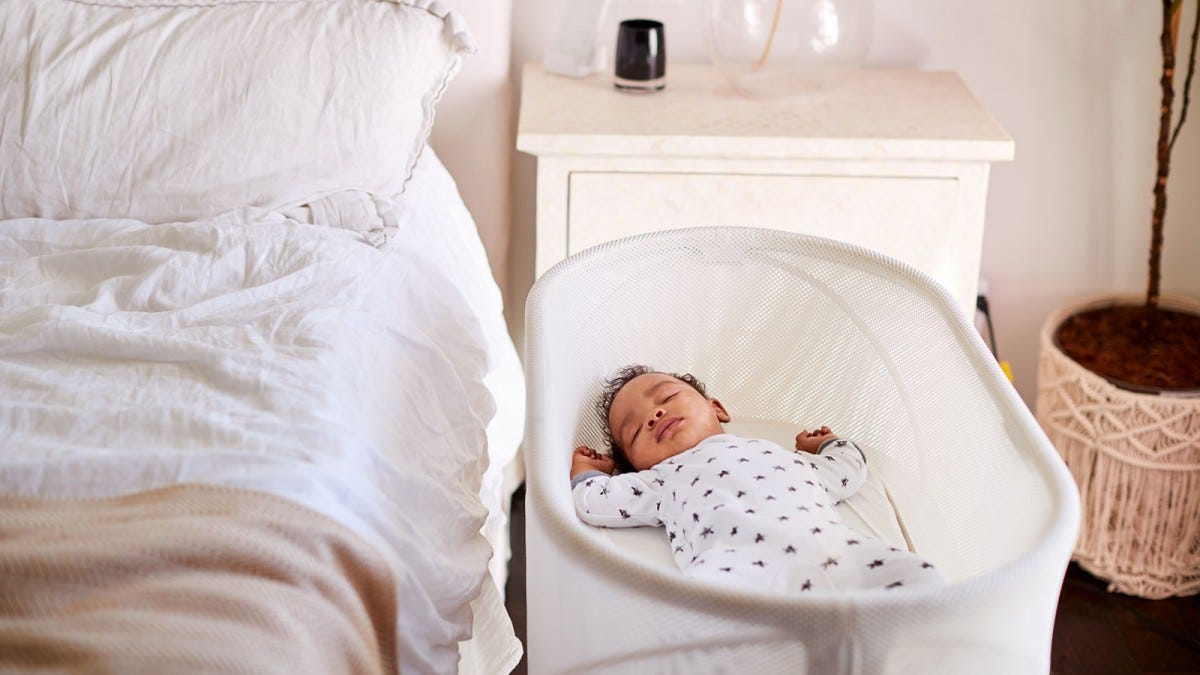 A baby sleeping in a bassinet.
