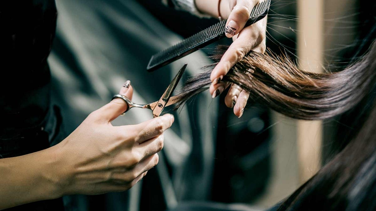 A woman's hands cutting long brown hair.