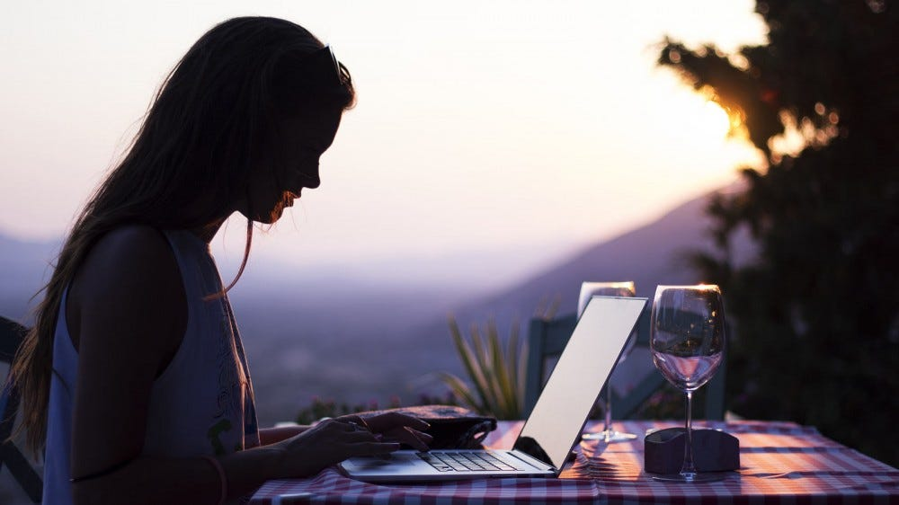 A woman working on a laptop outside at dusk.