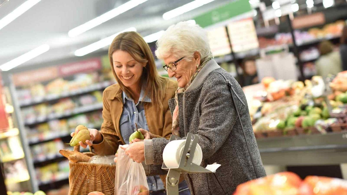 a young woman grocery shopping with an elderly woman