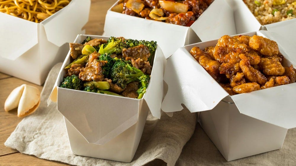 Chinese food in carry out containers on a wooden table.